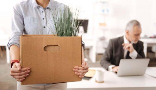 Jeune femme debout tenant une grosse boîte tout en quittant le bureau.